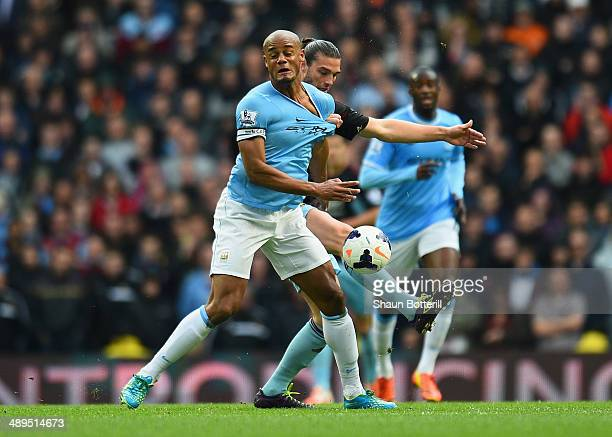 Vincent Kompany of Manchester City tangles with Andy Carroll of West Ham United during the Barclays Premier League match between Manchester City and...