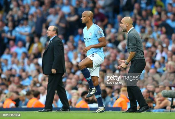 Vincent Kompany of Manchester City waits to come on as Pep Guardiola makes a substitution during the Premier League match between Manchester City and...