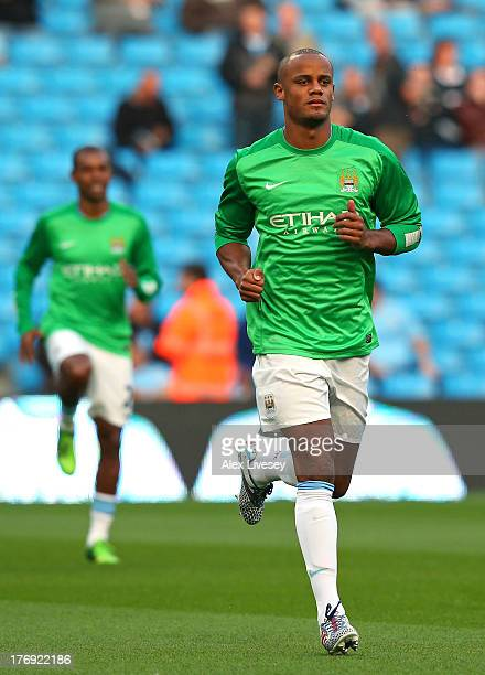 Vincent Kompany of Manchester City wears a goalkeeper shirt in memory of Bert Trautmann the former goalkeeper who died in July as he warms up prior...