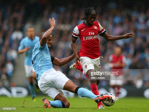 Vincent Kompany of Manchester Citytackles Gervinho of Arsenal during the Barclays Premier League match between Manchester City and Arsenal at Etihad...