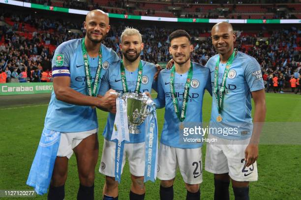 Vincent Kompany Sergio Aguero David Silva and Fernandinho of Manchester City celebrate victory with the trophy after the Carabao Cup Final between...