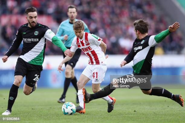 Vincent Koziello of Koeln is challenged by Kenan Karaman and Oliver Sorg of Hannover during the Bundesliga match between 1 FC Koeln and Hannover 96...