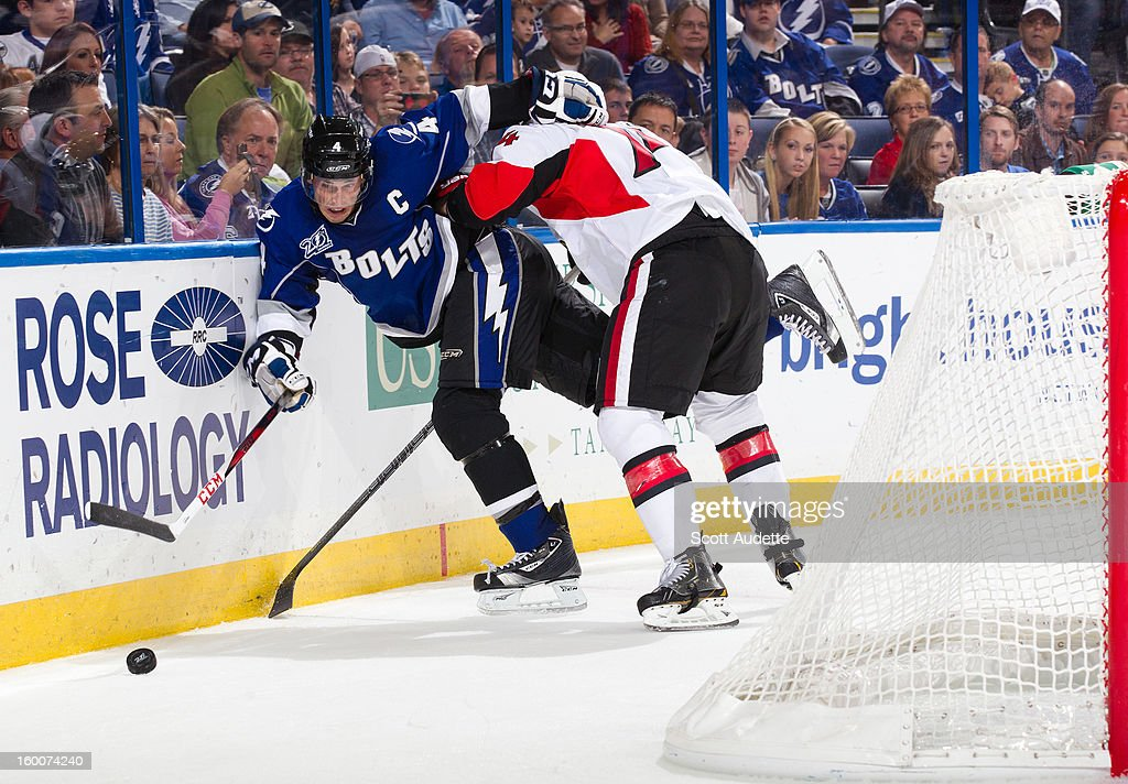 Vincent Lecavalier #4 of the Tampa Bay Lightning battles for the puck behind the net against Mark Borowiecki #74 of the Ottawa Senators during the third period at the Tampa Bay Times Forum on January 25, 2013 in Tampa, Florida.