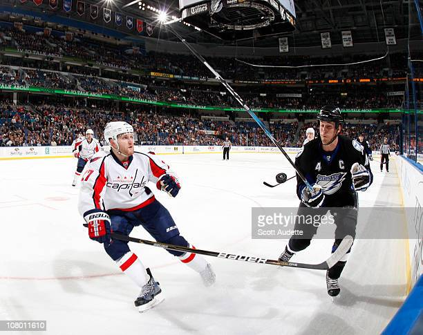 Vincent Lecavalier of the Tampa Bay Lightning blocks the puck as Karl Alzner of the Washington Capitals tries to clear it out of the zone during the...