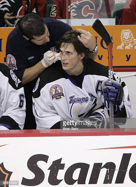 Vincent Lecavalier of the Tampa Bay Lightning is treated by medical personel after taking a hard hit from Ville Nieminen of the Calgary Flames during...