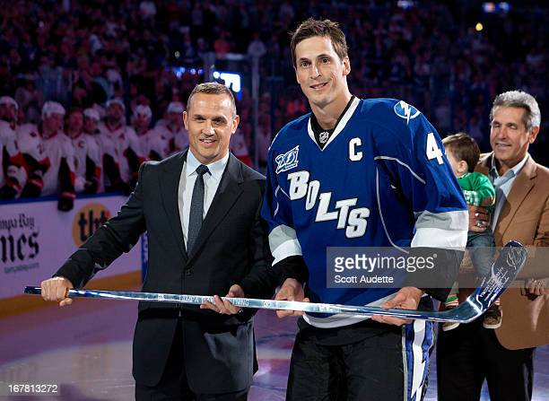 Vincent Lecavalier of the Tampa Bay Lightning receives a silver stick during his 1000th NHL game ceremony from Tampa Bay Lightning VP General Manager...