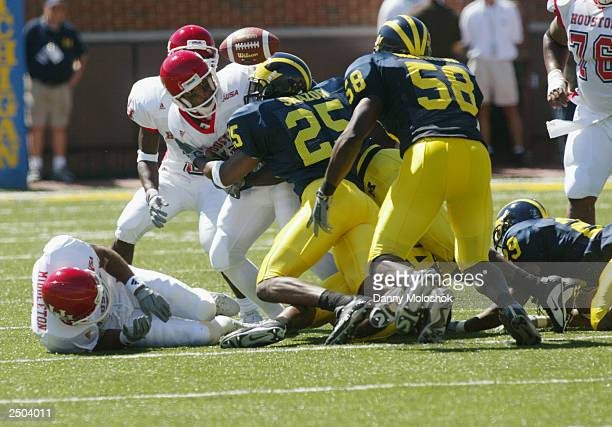 Vincent Marshall of the Houston Cougars fumbles the ball after a hit from Ernest Shazor Roy Manning and Leon Hall of the Michigan Wolverines on...