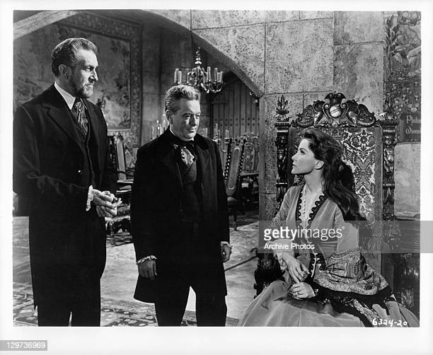 Vincent Price and Frank Maxwell looking at Debra Paget, who's sitting down, in a scene from the film 'Haunted Palace', 1963.