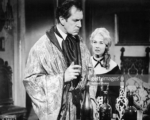 Vincent Price holding glass while Myrna Fahey looks at him in a scene from the film 'House Of Usher' 1953
