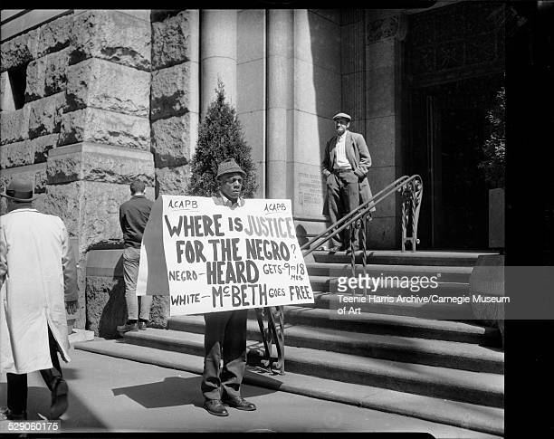 Vincent 'Roots' Wilson protesting in front of Allegheny County Courthouse with placard reading 'Where is justice for the Negro - Heard gets 9 to 18...