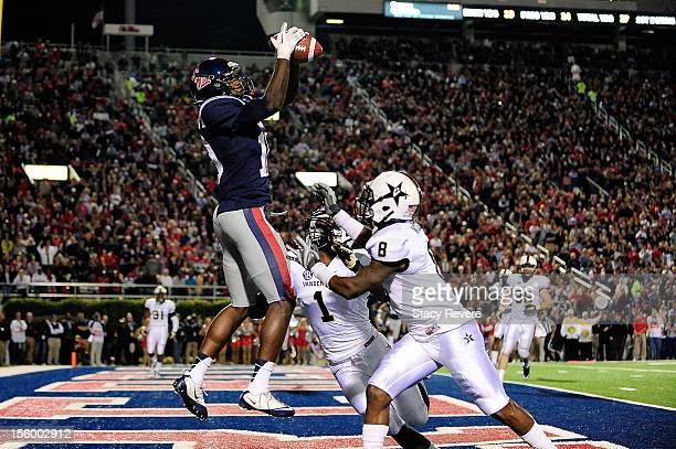 Vincent Sanders of the Ole Miss Rebels catches a touchdown pass over Kenny Ladler and Trey Wilson of the Vanderbilt Commodores during a game at...