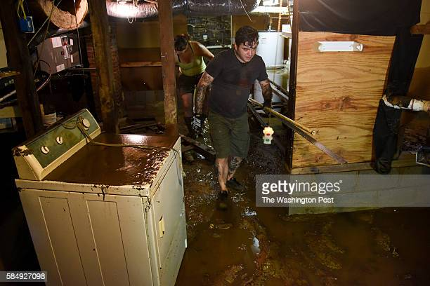 Vincent Saulsbury clears his flooded basement after heavy floods devastated the historic district of the town on Sunday July 31 in Ellicott City MD...