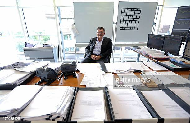 Vincent Tchenguiz, chairman of Consensus Business Group Ltd., poses for a photograph at his desk following a Bloomberg Television interview in his...