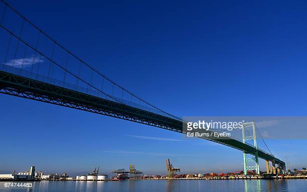 vincent thomas bridge over river against blue sky - port of los angeles stock pictures, royalty-free photos & images