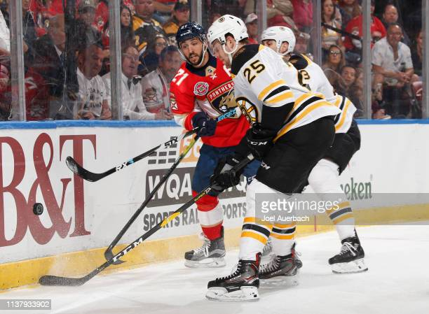 Vincent Trocheck of the Florida Panthers and Brandon Carlo of the Boston Bruins battle for control of the loose puck at the BBT Center on March 23...