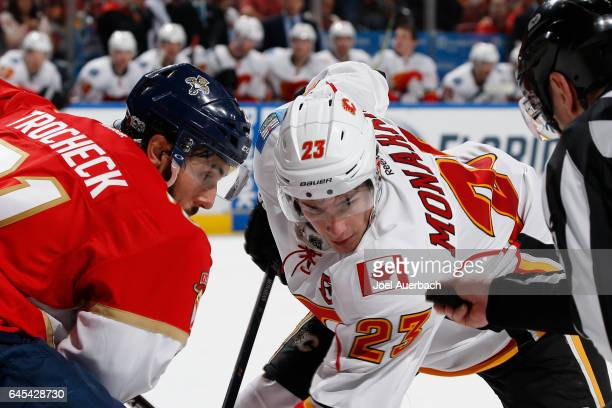 Vincent Trocheck of the Florida Panthers and Sean Monahan of the Calgary Flames wait for linesman Pierre Racicot to drop the puck at the BBT Center...