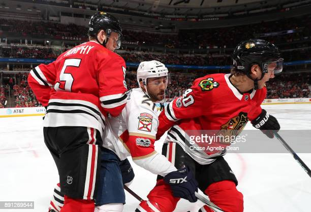 Vincent Trocheck of the Florida Panthers chases the puck against Connor Murphy and John Hayden of the Chicago Blackhawks in the third period at the...