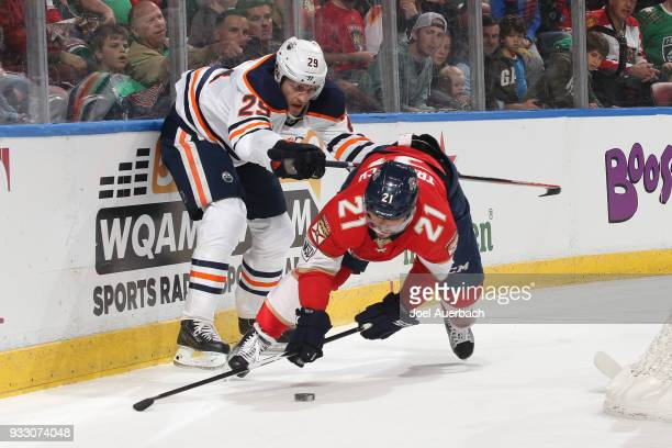 Vincent Trocheck of the Florida Panthers is taken to the ice by Leon Draisaitl of the Edmonton Oilers as he skates with the puck during first period...