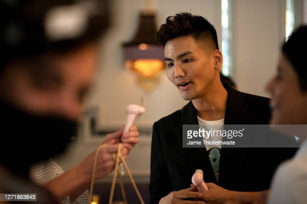 """Vincent Wong looks at a neon mini fan during the """"Henpire"""" podcast launch event at Langham Hotel on September 10, 2020 in London, England."""