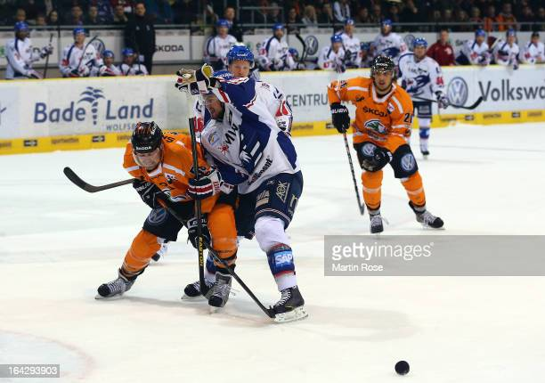 Vincenz Mayer of Wolfsburg and Dominik Bittner of Mannheim battle for the puck in game two of the DEL play-offs between Grizzly Adams Wolfsburg and...
