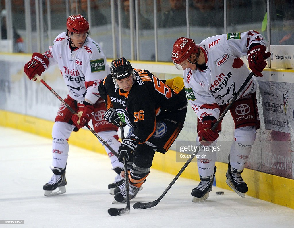 Vincenz Mayer of Wolfsburg is challenged by Moritz Mueller of Cologne during the DEL match between Grizzly Adams Wolfsburg and Kolner Haie at the Volksbank BraWo Eisarena on January 4, 2013 in Wolfsburg, Germany