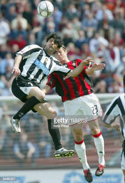 Vincenzo Iaquinta of Udinese and Massimo Ambrosini of Milan jump for the ball during a Seria A match between Milan and Udinese on April 25, 2004 at...