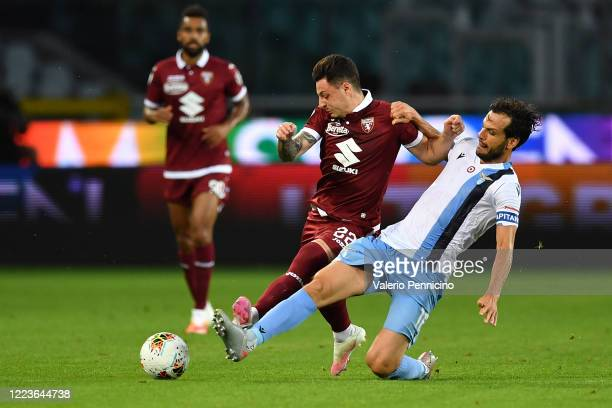 Vincenzo Millico of Torino FC is tackled by Marco Parolo of SS Lazio during the Serie A match between Torino FC and SS Lazio at Stadio Olimpico di...