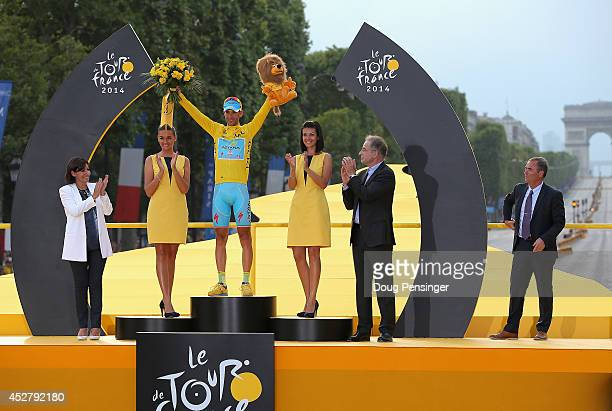 Vincenzo Nibali of Italy and Astana Pro Team celebrates victory in the yellow jersey on the podium following the twenty first stage of the 2014 Tour...