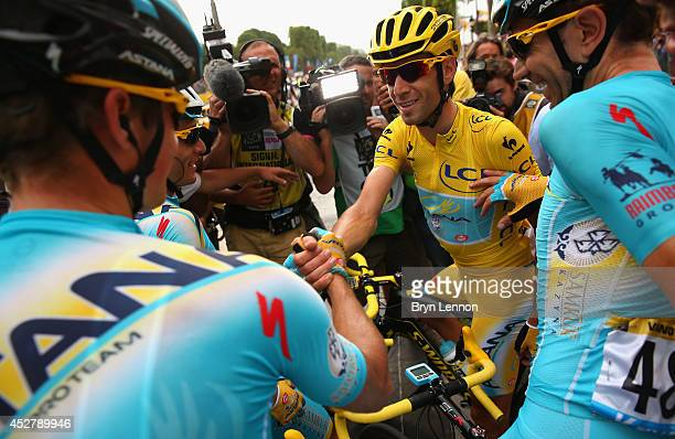 Vincenzo Nibali of Italy and Astana Pro Team celebrates victory with his team-mates following the twenty first stage of the 2014 Tour de France, a...