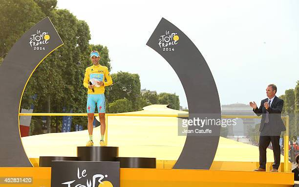Vincenzo Nibali of Italy and Astana Pro Team celebrates winning the yellow jersey on the podium while five time winner of the Tour de France Bernard...
