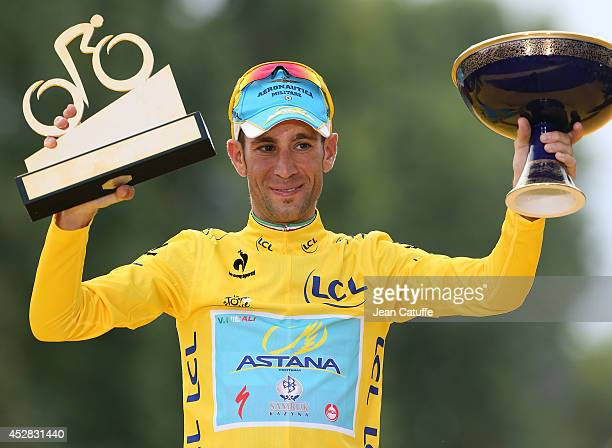Vincenzo Nibali of Italy and Astana Pro Team celebrates winning the yellow jersey on the podium, following the twenty one and last stage of the 2014...