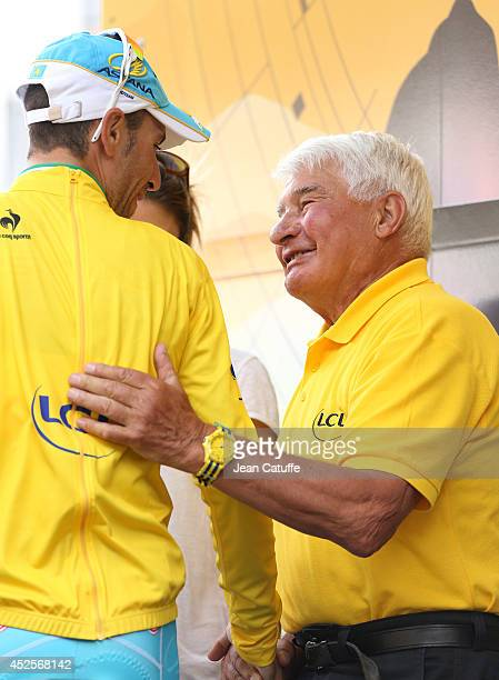Vincenzo Nibali of Italy and Astana Pro Team who retains the race leader's yellow jersey is congratulated by Raymond Poulidor on the podium after...