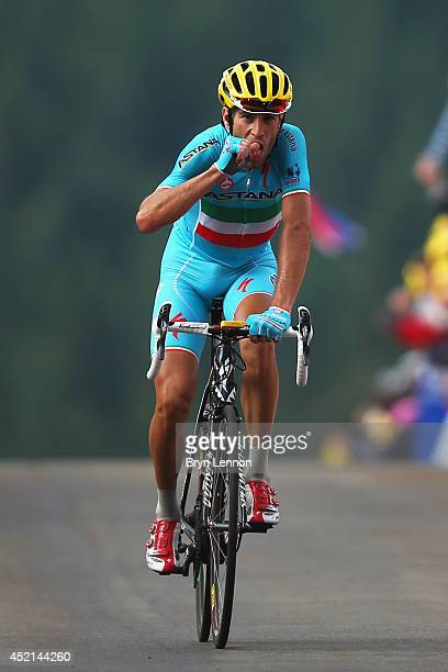 Vincenzo Nibali of Italy and the Astana Pro Team bites his thumb in honour of his recently born daughter as he celebrates crossing the finish line to...