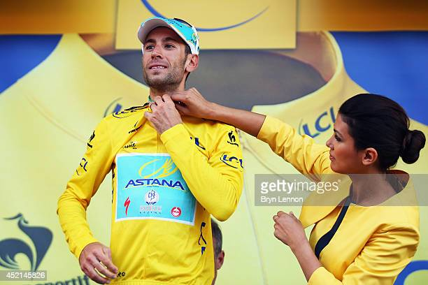 Vincenzo Nibali of Italy and the Astana Pro Team celebrates on the podium as he regains the overall race leader's yellow jersey after the tenth stage...