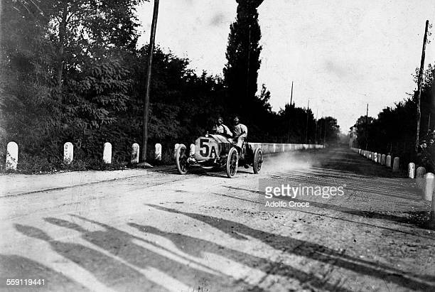 Vincenzo Trucco of Italy and his riding mechanic drives the Isotta-Fraschini past the shadows of watching spectators during the II Coppa Florio race...