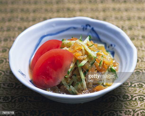 Vinegared jellyfish and strips of cucumber in bowl, high angle view, differential focus