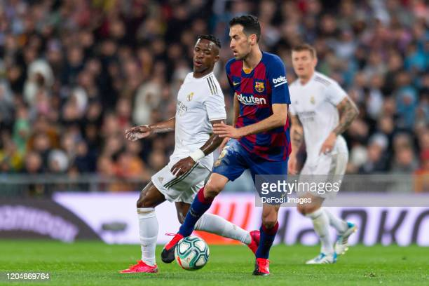 Vinicius Jr of Real Madrid and Sergio Busquets of FC Barcelona battle for the ball during the Liga match between Real Madrid CF and FC Barcelona at...