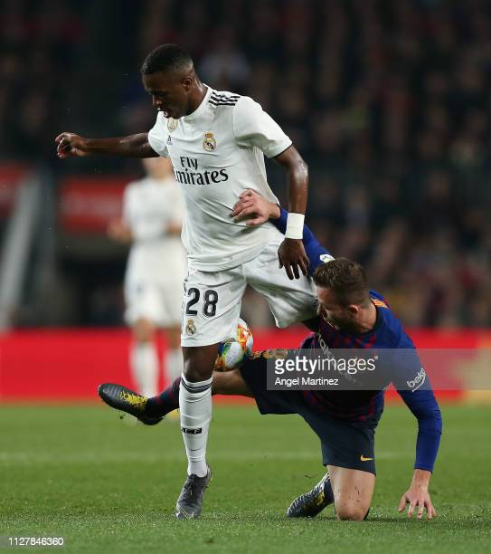 Vinicius JR of Real Madrid CF competes for the ball with Arthur Melo of FC Barcelona during the Copa del Semi Final first leg match between Barcelona...