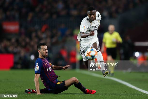 Vinicius JR of Real Madrid CF competes for the ball with Sergio Busquets of FC Barcelona during the Copa del Semi Final first leg match between...