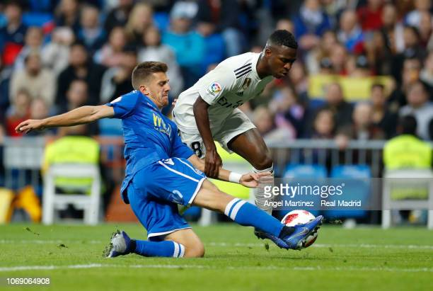 Vinicius Jr of Real Madrid competes for the ball with Pepe Romero of Melilla during the Copa del Rey fourth round second leg match between Real...