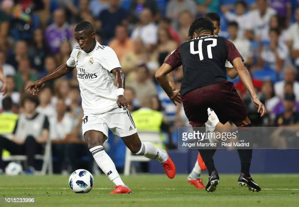 Vinicius Jr of Real Madrid is challenged by Raoul Bellanova of AC Milan during the Trofeo Santiago Bernabeu match between Real Madrid and AC Milan at...
