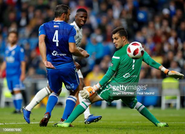 Vinicius Jr of Real Madrid scores his team's fifth goal past Pedro Luis Moreno and Richi Segura of Melilla during the Copa del Rey fourth round...
