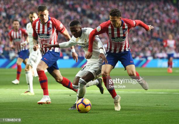 Vinicius Junior of Real Madrid battles for possession with Santiago Arias of Atletico Madrid during the La Liga match between Club Atletico de Madrid...