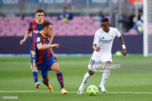 Vinicius Junior of Real Madrid CF runs with the ball under pressure from Sergino Dest of FC Barcelona during the La Liga Santander match between FC...