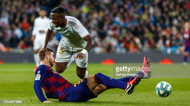 Vinicius Junior of Real Madrid Gerard Pique of FC Barcelona battle for the ball during the Liga match between Real Madrid CF and FC Barcelona at...