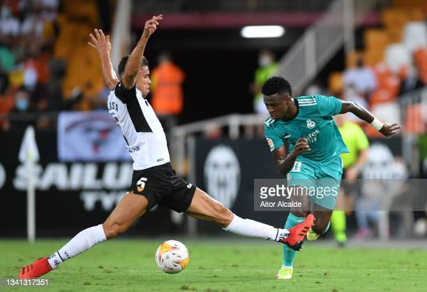 Vinicius Junior of Real Madrid is challenged by Gabriel Paulista of Valencia during the La Liga Santander match between Valencia CF and Real Madrid...