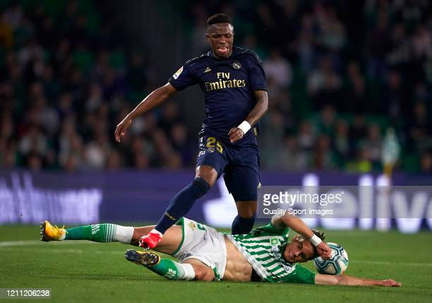 Vinicius Junior of Real Madrid is tackled by Marc Bartra of Real Betis during the Liga match between Real Betis Balompie and Real Madrid CF at...