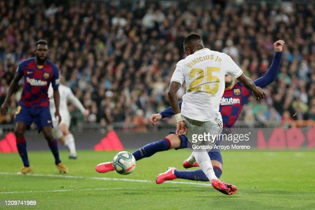 Vinicius Junior of Real Madrid scores his team's first goal past Gerard Pique of FC Barcelona during the Liga match between Real Madrid CF and FC...