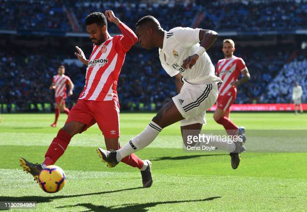 Vinicius Junior of Real Madrid shoots past Jonas Ramalho of Girona FC during the La Liga match between Real Madrid CF and Girona FC at Estadio...
