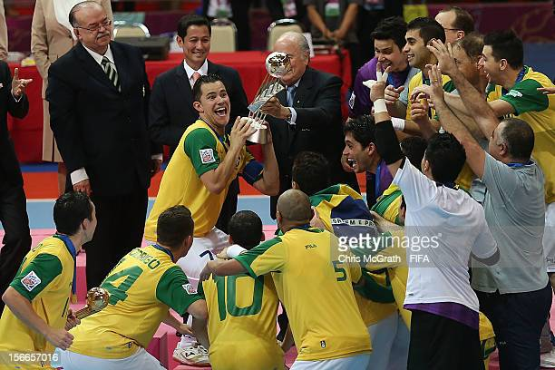 Vinicius of Brazil receives the trophy from FIFA President Joseph S Blatter after defeating Spain during the FIFA Futsal World Cup Final between...
